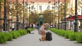 Ung kvinna med resväskan som går ner gatan i en europeisk stad arkivfilmer