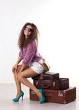 Ung kvinna med resväskor arkivbild