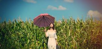 Ung kvinna med resväskan och paraplyet Arkivbild