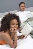Ung kvinna med romanen i sovrum Royaltyfri Fotografi