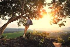 Ung kvinna med ryggsäckanseende på kanten av en klippa. Royaltyfria Foton