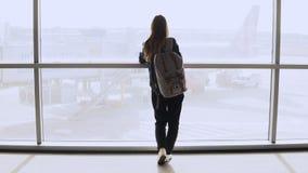 Ung kvinna med ryggsäcken nära slutligt fönster Caucasian kvinnlig turist- användande smartphone i flygplatsvardagsrum Resor 4K royaltyfri foto