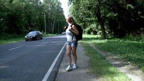 Ung kvinna med ryggsäcken och solglasögon som går på vägen arkivfilmer