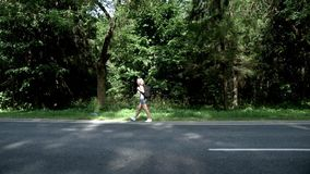 Ung kvinna med ryggsäcken som går på vägen på sikt för skogbakgrundssida stock video