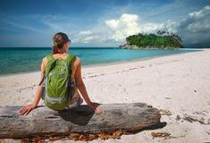 Ung kvinna med ryggsäcken som kopplar av på kust och ser till en isl Royaltyfri Fotografi