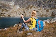 Ung kvinna med ryggsäcken som sitter nära bergsjön arkivfoto