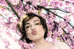 Ung kvinna med sakura blommor, blått filter fotografering för bildbyråer