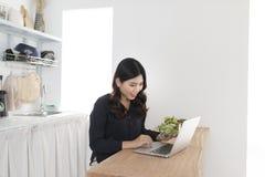 Ung kvinna med sallad som arbetar på bärbara datorn i köket royaltyfria bilder