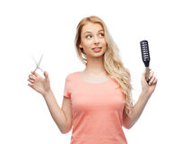Ung kvinna med sax och hårborsten royaltyfria foton