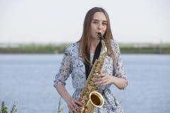 Ung kvinna med saxofonen med naturbakgrund fotografering för bildbyråer