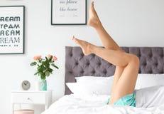 Ung kvinna med sexiga ben som vilar på säng arkivbilder