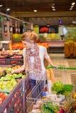 Ung kvinna med shoppingkorgen som väljer äpplen royaltyfri fotografi
