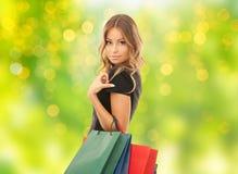Ung kvinna med shoppingpåsar över ljus arkivbilder