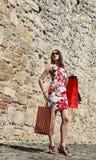 Ung kvinna med shoppingpåsar i en stadsgata Royaltyfri Fotografi