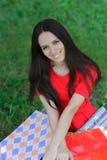 Ung kvinna med shoppingpåsar och gräs Royaltyfria Bilder