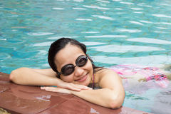 Ung kvinna med simningexponeringsglas som ler i pöl Arkivfoton