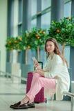 Ung kvinna med smartphonen i internationell flygplats Flygbolagpassagerare i flygplan för flyg för flygplatsvardagsrum ett väntan arkivbilder
