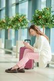 Ung kvinna med smartphonen i väntande på flyg för internationell flygplats arkivfoton