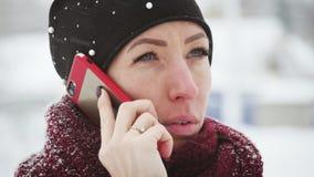 Ung kvinna med smartphonen och vinterlandskapet som är utomhus- Flickan som använder den utomhus- mobila smartphonen, snö faller arkivfilmer