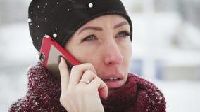 Ung kvinna med smartphonen och vinterlandskapet som är utomhus- Flickan som använder den utomhus- mobila smartphonen, snö faller stock video