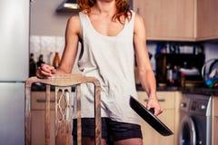 Ung kvinna med stekpannan i kök fotografering för bildbyråer