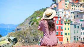 Ung kvinna med stor sikt på den gamla byn Riomaggiore, Cinque Terre, Liguria, Italien Europeisk italiensk semester stock video