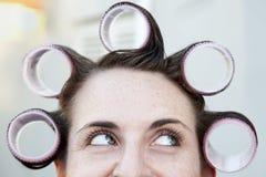 Ung kvinna med stora hårrullar i hennes hår Fotografering för Bildbyråer