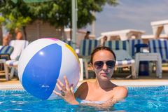 Ung kvinna med strandbollen i simbassäng Fotografering för Bildbyråer