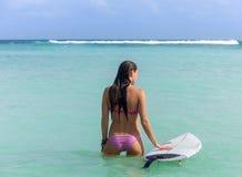 Ung kvinna med surfingbrädan i havet Arkivfoto