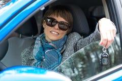 Ung kvinna med tangenterna i bilen Arkivbild