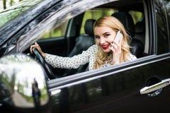 Ung kvinna med telefonen som har telefonkonversation, medan köra bilen på stadsgatan royaltyfri foto