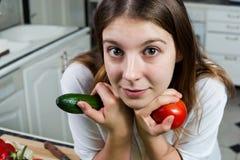 Ung kvinna med tomaten och gurkan Royaltyfri Bild