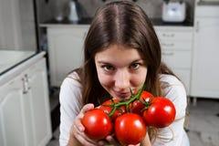 Ung kvinna med tomatnärbild på kök Arkivbilder