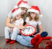 Ung kvinna med två döttrar som ser hans klocka Fotografering för Bildbyråer