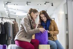 Ung kvinna med vännen som ser in i shoppingpåse på lagret Arkivfoto