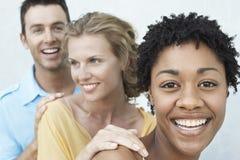 Ung kvinna med vänner som har gyckel tillsammans Arkivfoto