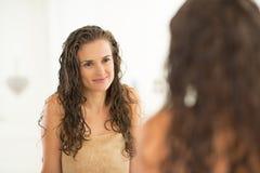 Ung kvinna med vått hår som ser i spegel arkivbild
