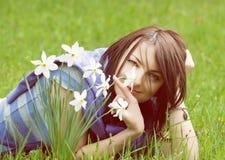 Ung kvinna med vita påskliljor, gult filter Royaltyfria Bilder