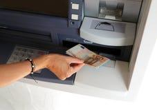 Ung kvinna, medan återta sedlar från en ATM Arkivfoton