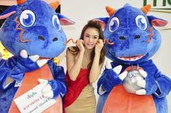 Ung kvinna mellan 2 maskotar på TCC-expoen 2012 Royaltyfri Bild