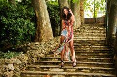 Ung kvinna, modell av mode, i trädgårds- trappa royaltyfri foto