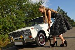 Ung kvinna nära den vita gamla bilen Royaltyfri Fotografi