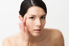 Ung kvinna observera ansiktsbehandlingskrynklor Arkivbilder