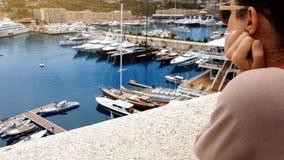 Ung kvinna observera yachter i port och att drömma av oligarch och rikt liv royaltyfri bild