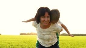 Ung kvinna och barn som har roligt utomhus Härlig familjmamma och hennes pojkepojke som tillsammans kramar och kysser Mammauppehä lager videofilmer