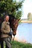 Ung kvinna och brunthäst tillsammans på flodkusten Royaltyfria Bilder