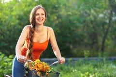 Ung kvinna och cykel Arkivbilder