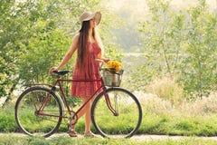Ung kvinna och cykel Arkivfoton