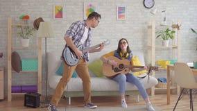 Ung kvinna och ung en man som spelar känslomässigt gitarren arkivfilmer