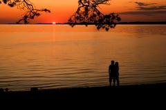 Ung kvinna och hållande ögonen på solnedgång för man Royaltyfria Foton